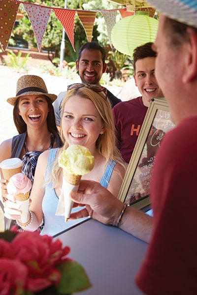 Happy Curtin students being served ice cream cones