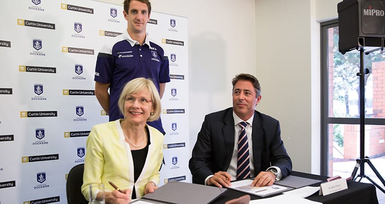 Vice-Chancellor Professor Deborah Terry, Fremantle Dockers player, Michael Barlow and Fremantle Dockers CEO Steve Rosich signing the agreement