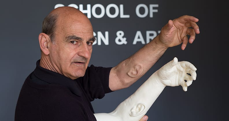 Professor Stelarc revealing his implanted third ear on his forearm