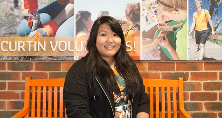Annika Htun sitting on a bench in front of a Curtin Volunteers! sign.