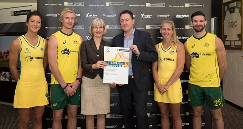 Vice Chancellor Professor Deborah Terry and Hockey Australia Chief Executive Cam Vale surrounded by two Hockeyroo players and two Kookaburra players