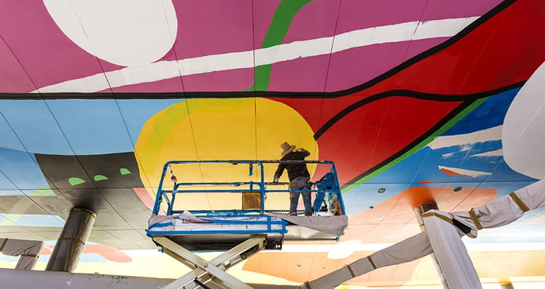 Artist paints colourful roof atop a cherry picker.