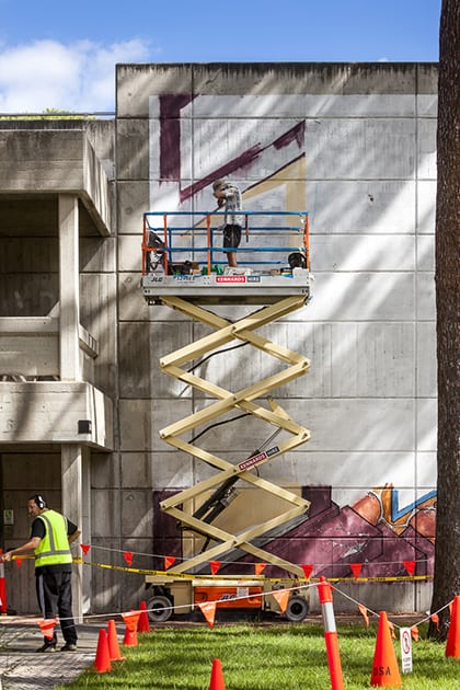 Two artists work on their murals outside.