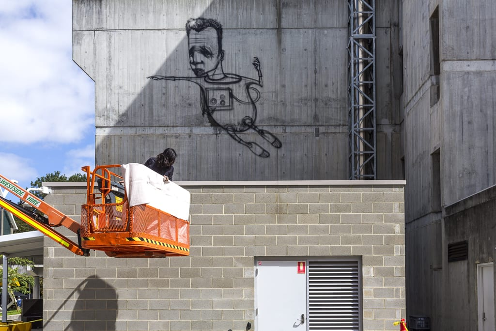 Artist in cherry picker with developing artwork of an astronaut in background.