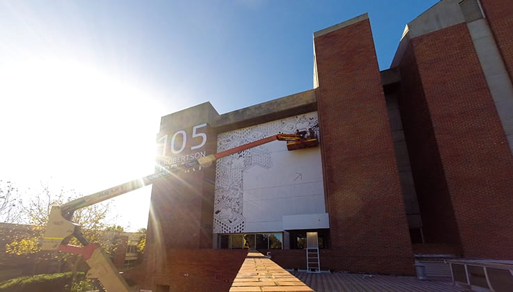 artist works on black and white mural on the side of Robertson Library from cherry picker