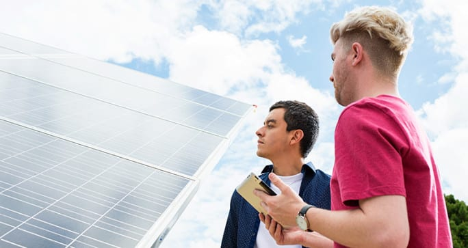 Two Curtin University researchers studying a solar panel