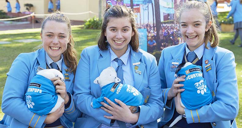 Three St Hilda students hold a puppy.