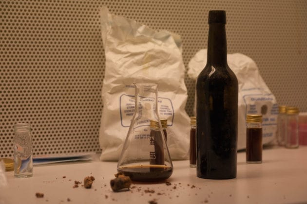 A beaker containing some of the bottle's contents, and its disintegrated cork in the foreground.