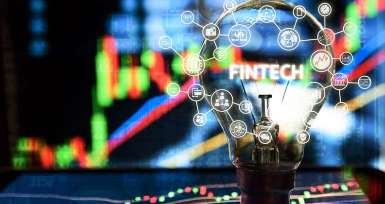 Lightbulb with the word Fintech captured inside it, surrounded by icons and stock graphs