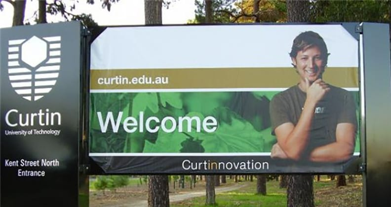 A younger Luke smiling from a Curtin billboard.