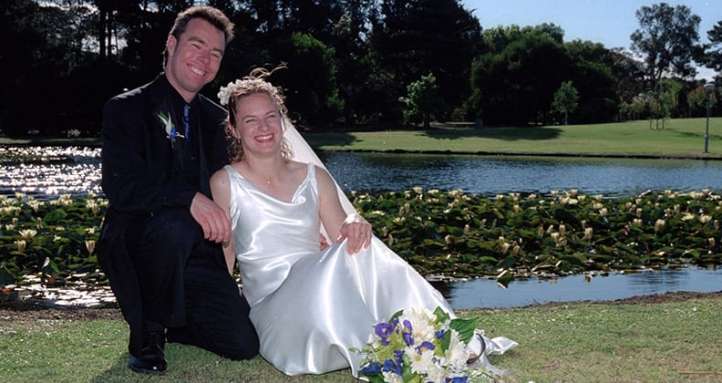 Martin and Tiffany on their wedding day in front of a grassy lake.