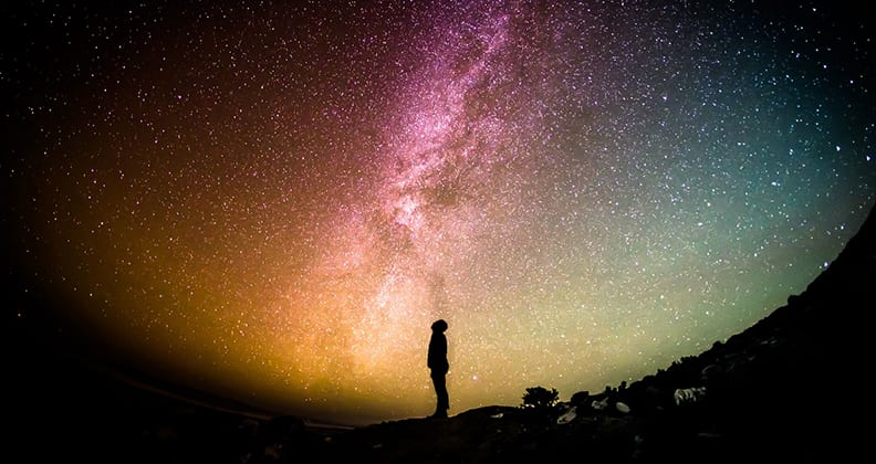 Person silhouetted against the Milky Way.