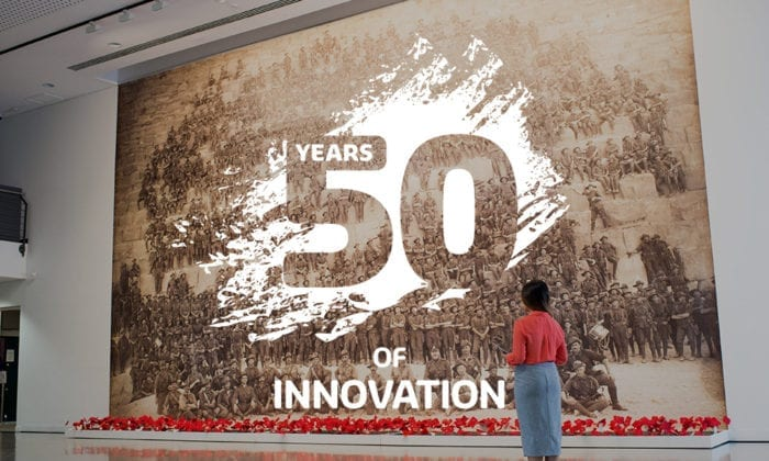50 Years of Innovation logo overlapping an image of a women looking at a art piece at the John Curtin Gallery