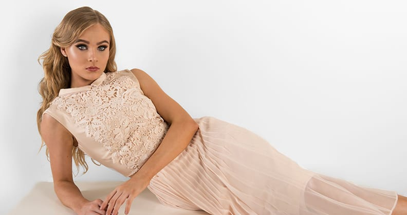 Model wears long pleated dress with lace embroidery.