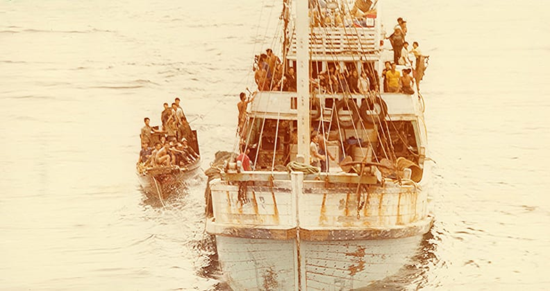 A sepia photograph of a boat filled with people.