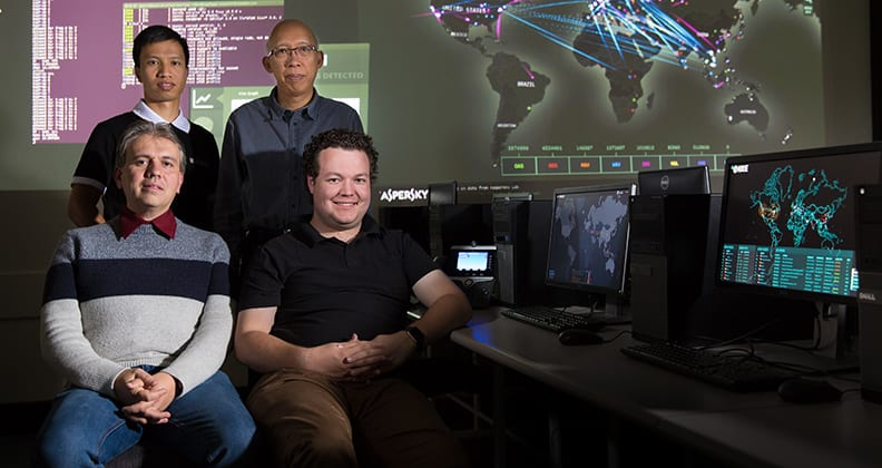 Winners of the 2017 Curtinnovation Awards grouped together in a dark room with computers.