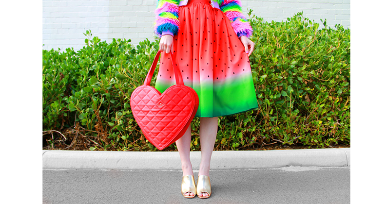 Kate Hannah in a watermelon dress and heart shaped hand bag.