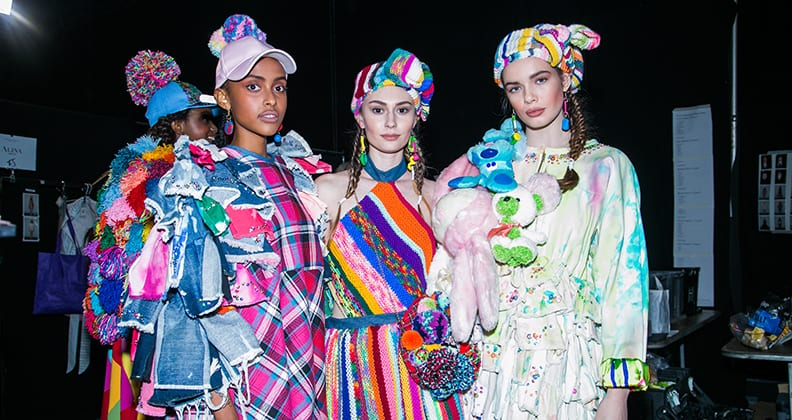 Three models wearing bright clothing made from denim, tartan, wool and toys.