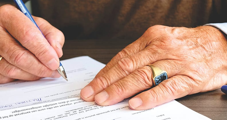 Close up of an elderly hand signing a form