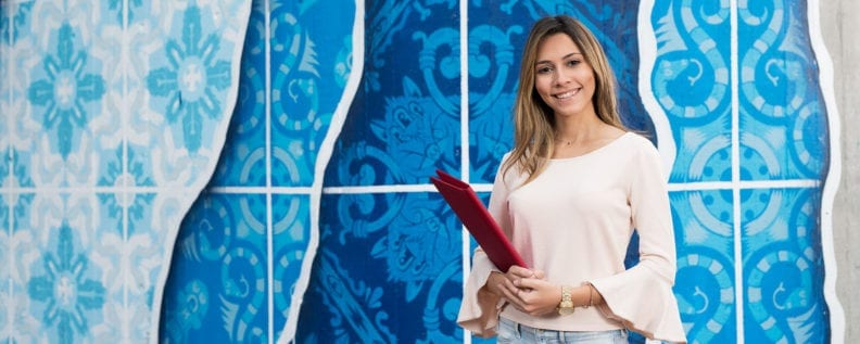 humanities student holding folder in front of blue painted background