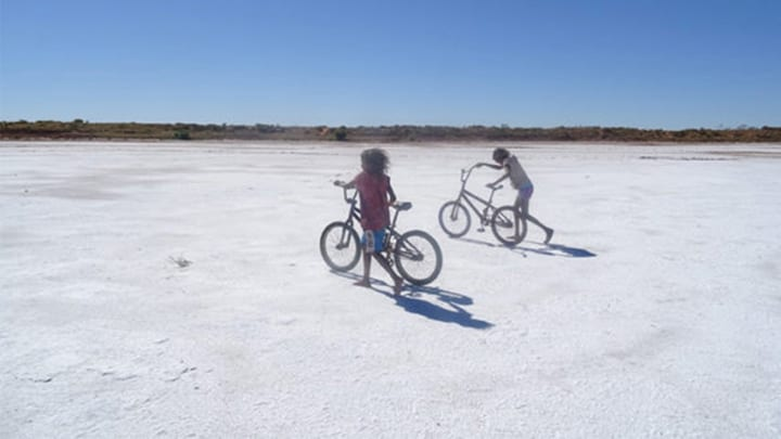 Indigenous children playing with bikes