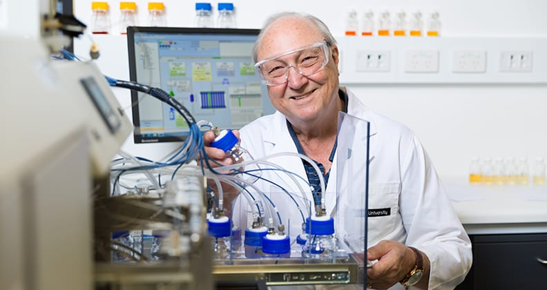 Professor Neil Foster working in his laboratory, holding a glass instrument