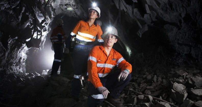 2 mining students in a mine, looking at the mine walls