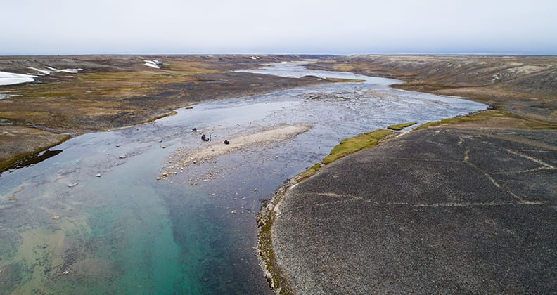 Crump and her team cross a wide, stone strewn river on Baffin Island.