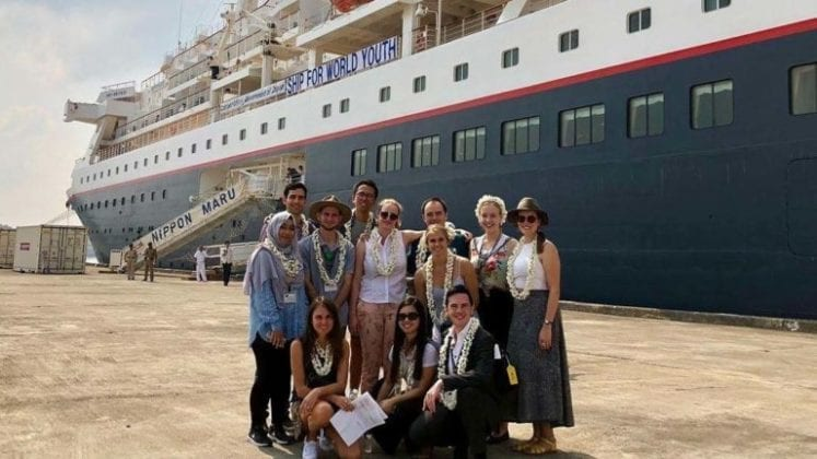 Students pose in front of cruise ship