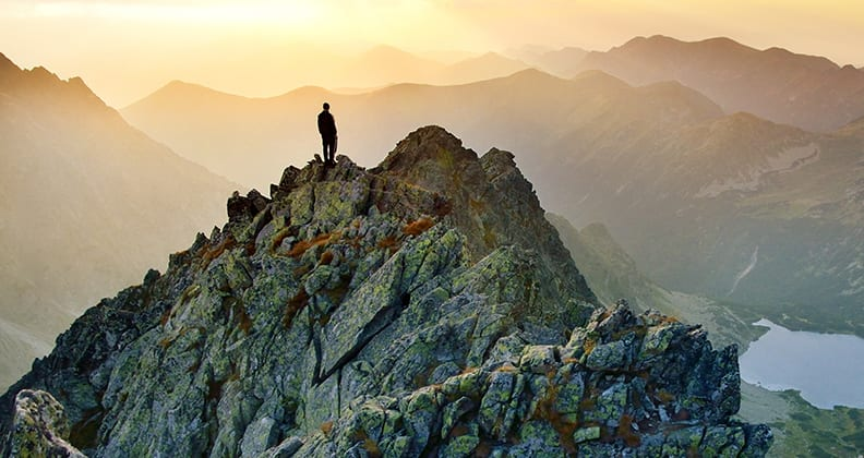 Hiker standing on top of a mountain