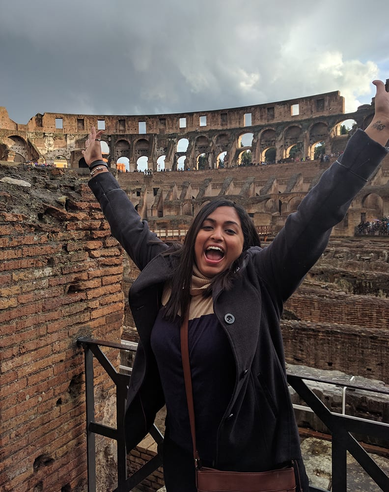 Swati with her hands in the air at the Colosseum in Rome.
