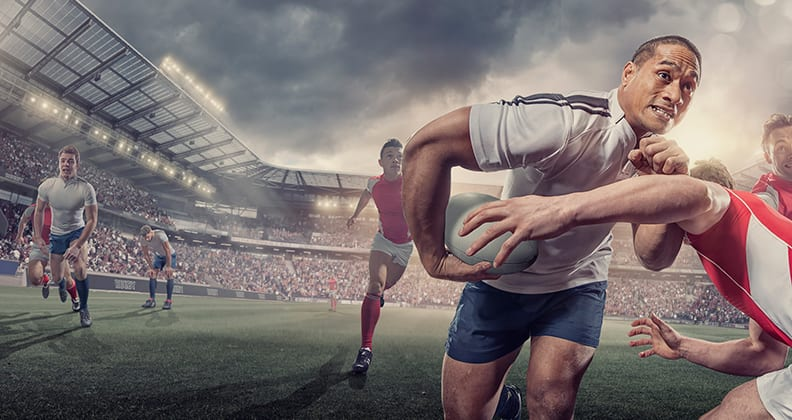 Rugby player running to end of field and getting tackled by another player.