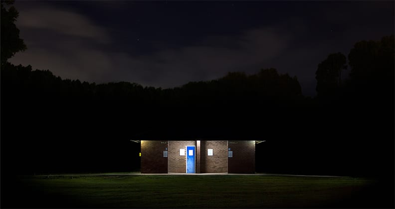 Underexposed shot of a toilet block at night, with the lights of the block illuminating the male and female entrances.