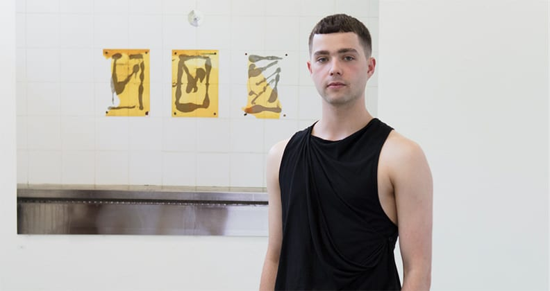 Ben Bannan, a young boy in a black singlet standing infront of a white background with three yellow prints.