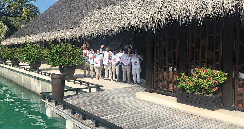 Eight staff hold a welcome sign beneath a large bungalow beside the water's edge.