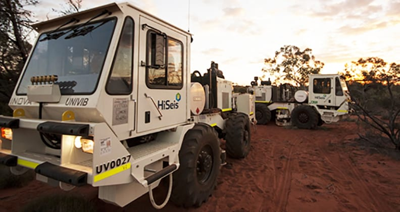 Two HiSeis trucks parked in the Australian scrub with sun setting behind them.