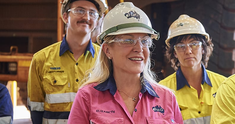 Elizabeth Gaines stands alongside her Fortecue team members, all wearing high vis workwear and hard hats.