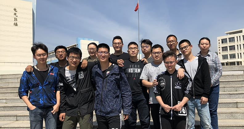 Postgraduate students from Yanshan University standing in their hometown in front of a flag and buildings.
