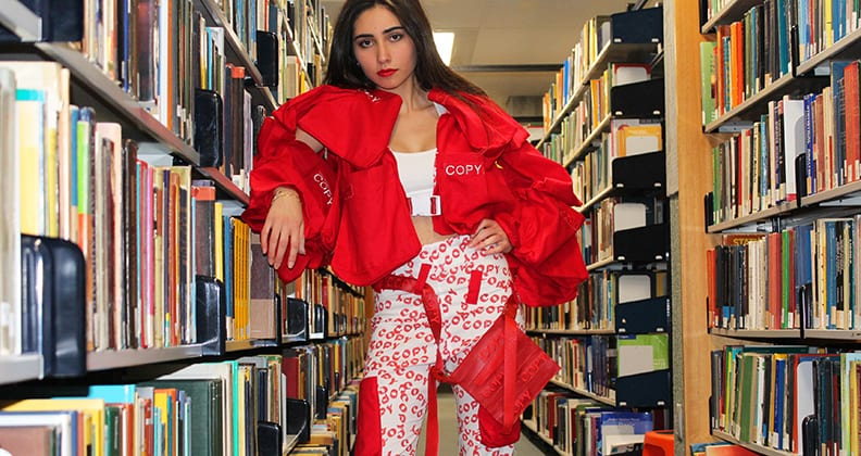 A yong girl leans against a library bookshelf wearing a bright, structured red jacket and white pants with the word 'Copy' printed over them.