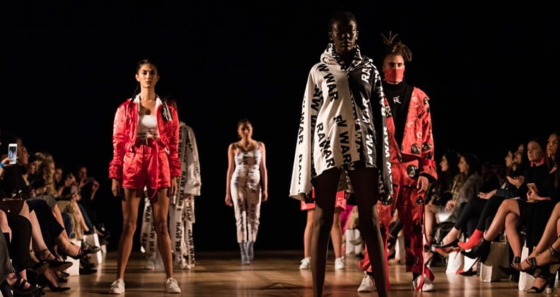 Five models stand on a dark catwalk wearing red, white and black clothing.
