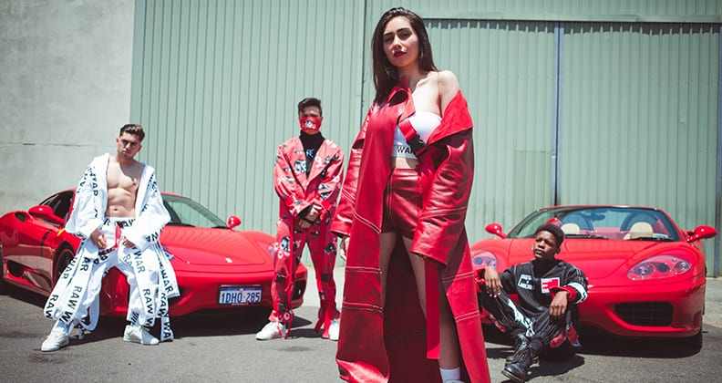 A yong girl stares down assertively at the camera in a floor length red leather jacket. Three young men pose on red sports cars behind her.
