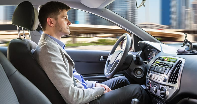 male sitting behind the wheel of an autonomous car