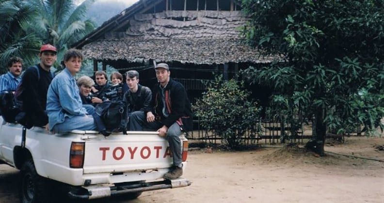 A photograph of eight young people with backpacks and camera gear are piled in the tray of a Toyota ute on the Thai-Burma border, 1992.
