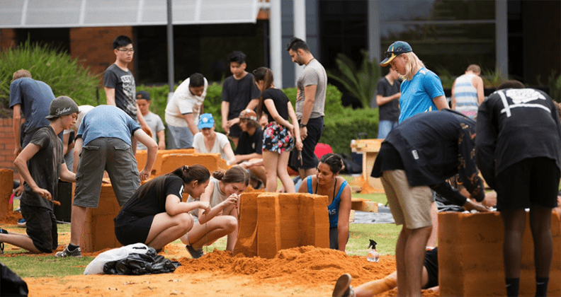Students crafting their sand sculptures