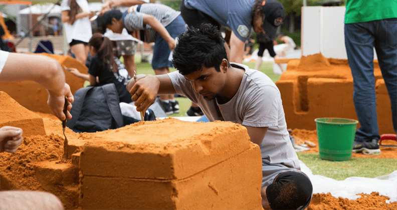 A single student carving a sand sculpture